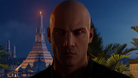Agent 47 walking towards the camera, a tower in the background