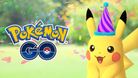 Pikachu wearing a festive hat standing next to a Pokemon GO logo