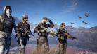 Ghost Recon Wildlands soldiers are standing in grass with their weapons at the ready.