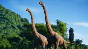Two dinosaurs are walking around in Jurassic World Evolution