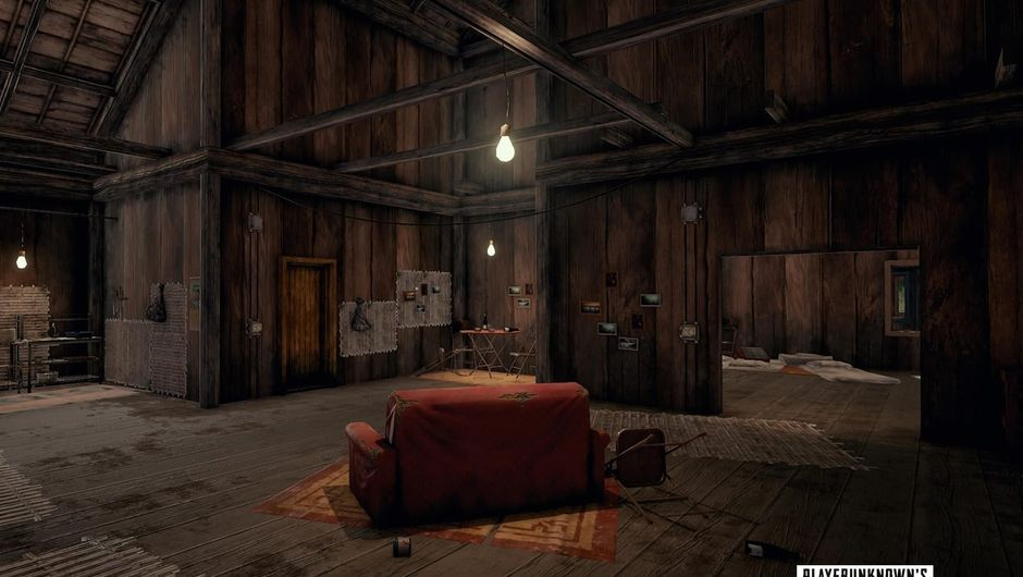A wooden barn with a couch inside from PUBG map Sanhok