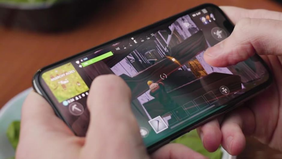 Hands holding a phone with the user playing Fortnite iOS