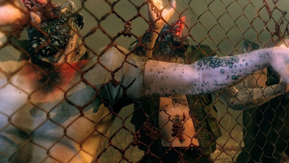 Weird looking zombies hugging a fence.