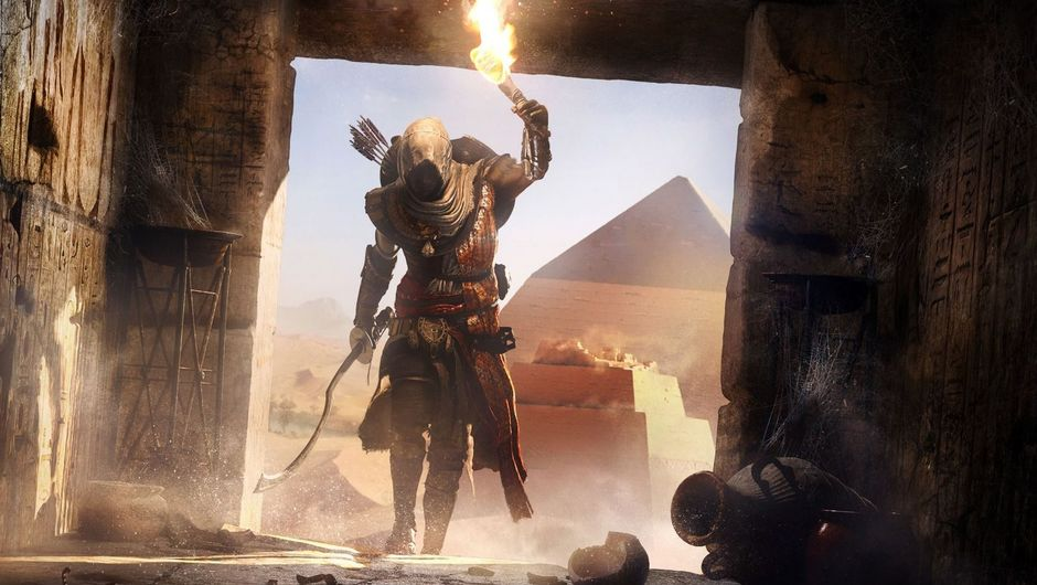Bayek walking into a pyramid with a torch