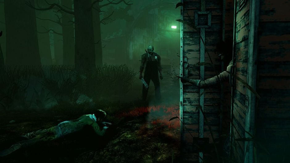 A killer is standing in a green mist in a dark environment.