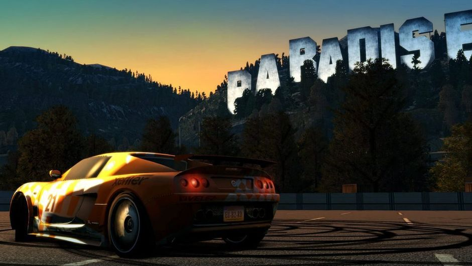 Yellow racing car parked below a hill that has letters spelling Paradise City on it.