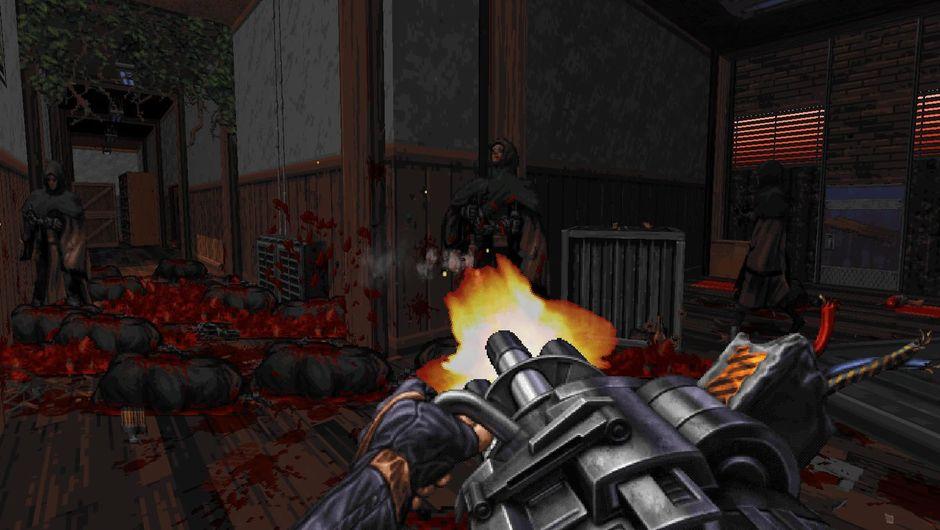 A hand holding a minigun shooting at creatures in a corridor
