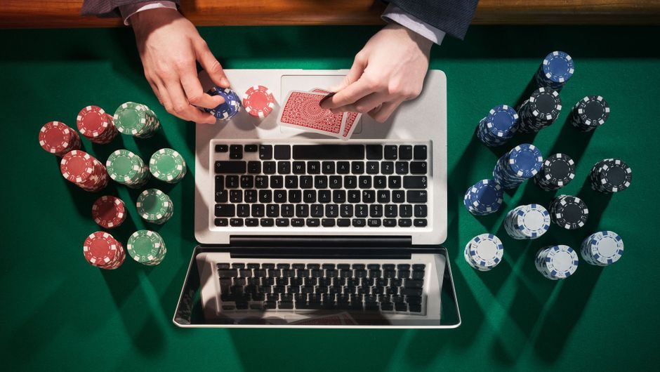 A man playing online poker in front of a laptop on a green table with chips all around