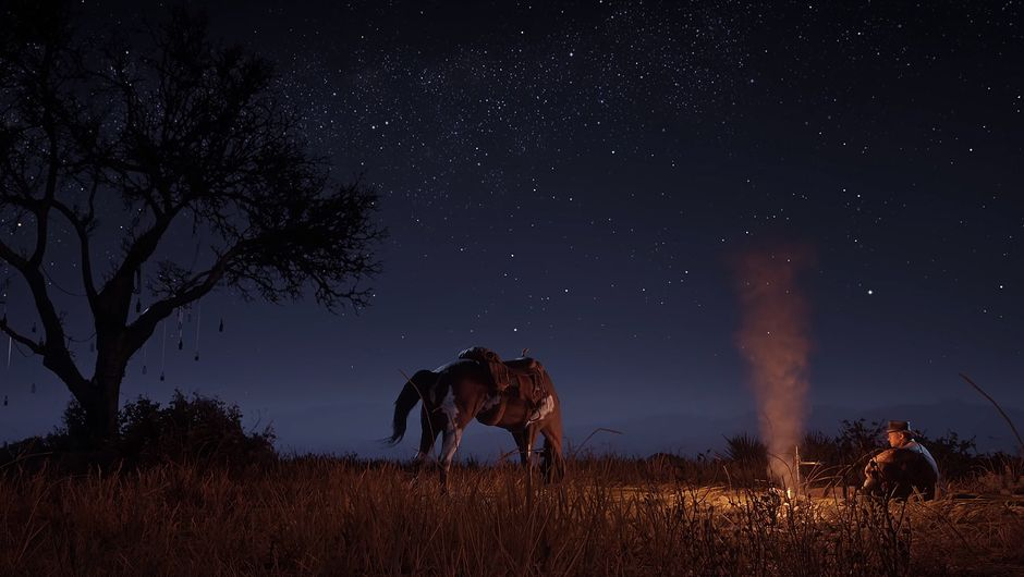 red dead redemption 2 screenshot showing a man sitting at the camp fire during night