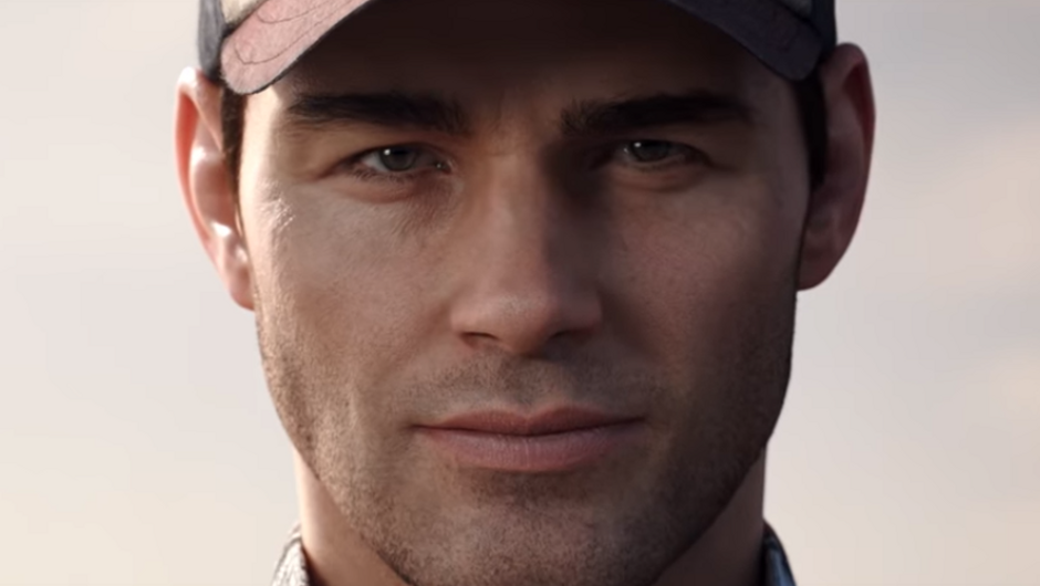 A close-up of a man with a baseball cap on his head, slightly smiling