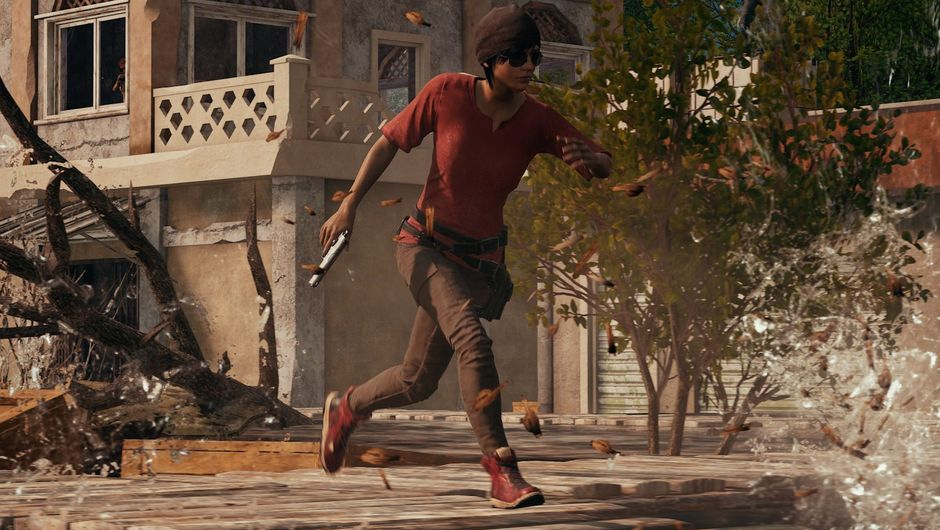 Some person is running around in a red shirt with a gun in her hand