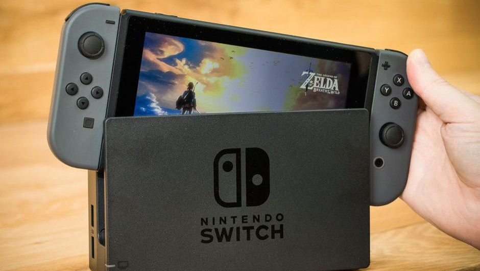 Nintendo Switch console being placed in a holder on a wooden table.