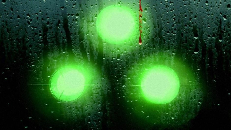 Sam Fisher's signature nocturne vision goggles are seen through a rainy glass.