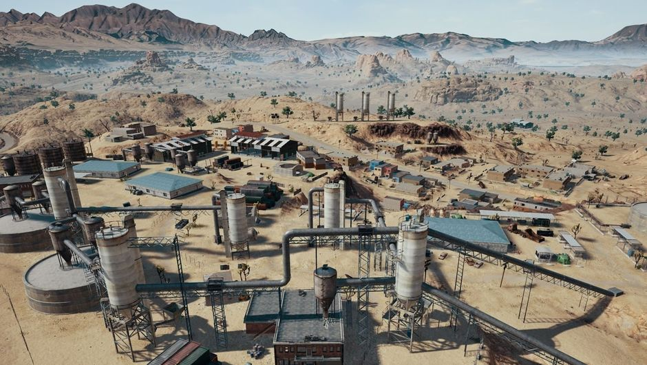 PlayerUnknown's Battlegrounds desert map - Miramar. Aerial view. Abandoned industry zone. Mountains in the backdrop.