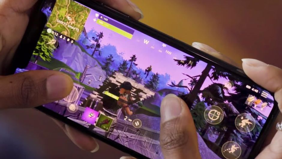 Hands holding a phone running Fortnite: Battle Royale iOS