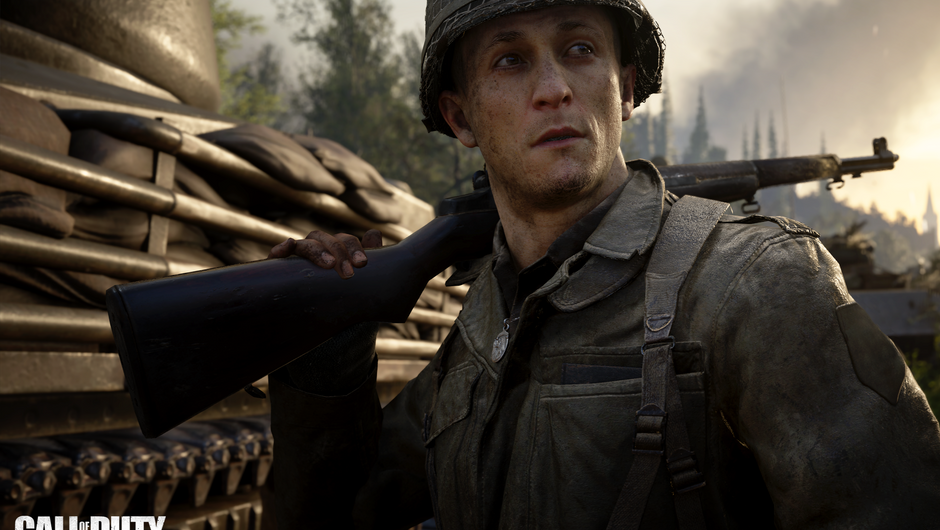 A soldier standing next to a tank, with a rifle on his shoulder, looking into the distance